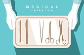 Assistant of the surgeon holds surgical instruments