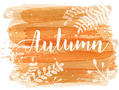 """Orange brushed lines  background with handwritten modern calligraphy text """"Autumn"""" and  floral botanical leaves decorations."""