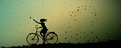 autumn rain, girl riding on the bicycle and autumn leaves swirling and rain started, silhouette, weather changing autumn come, vector