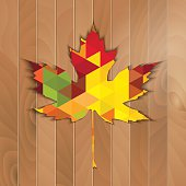 Autumnal Maple Leaf triangle on a wooden background