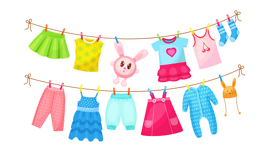 Baby clothes hanging on clothesline. Drying children's clothes and accessories after washing on rope. Shorts, socks, romper, sweater, hat, toys, T-shirt, sarafans, dress, skirts, blouse cartoon