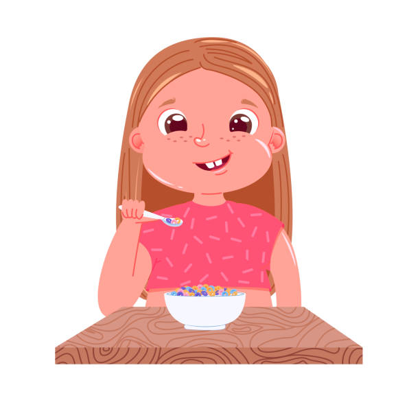 d0a2773e7 A baby girl eats breakfast in the morning. Sweet dish colourfull corn  flakes with milk
