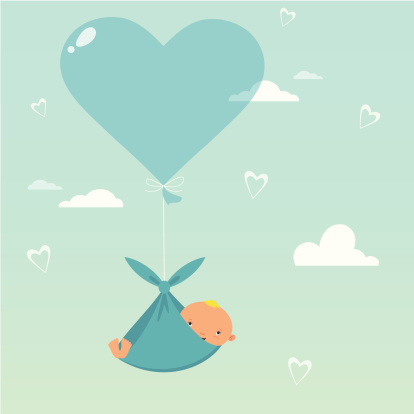 Baby hanging in a sling from a blue heart balloon