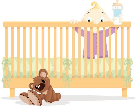 Baby in Crib looking at Teddy Bear