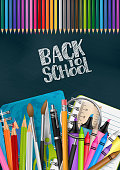 Back to school poster with colorful supplies - coloring pencils, pen, brushes, markers, ring notebooks, crayons. Blue textured chalkboard flyer background. Realistic vector illustration.