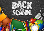 Vector illustration of Back to School with school supplies and doodles on black chalkboard background