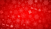 Christmas background of big and small snowflakes and various Christmas symbols, white on red