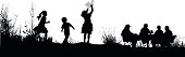 A vector silhouette illustration of chrildren playing in a field near adults sitting at a table.