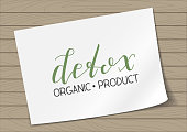 Badge Detox Organic Product with Hand Drawn Lettering on A4 Sheet Paper on Wooden Background. Green Emblem Vector Illustration.