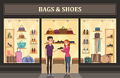 Bags and shoes shop with glassware showcase. Man buying footwear