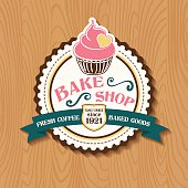 Bake Shop or Cafe Sticker With Cupcake and Ribbon. There is a wooden background with lots of grain. Several layers for easy editing.