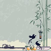 Two birds by a little bird feeder hanging from bamboo in a pot and oranges are ripening in the sun. Retro style.