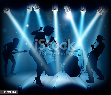 A band playing music at a live concert  on a stage with spotlights in silhouette