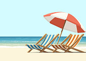 Summer, sun, waves, and cozy beach chairs under umbrella
