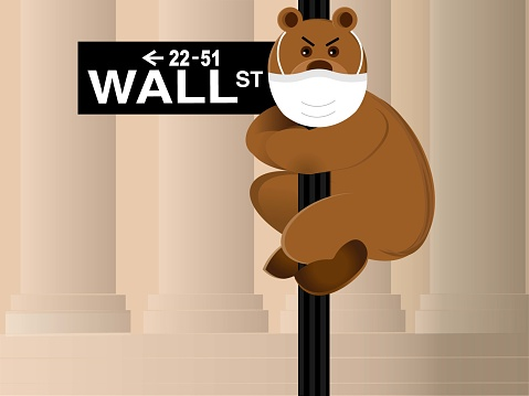 Bear wearing protective mask hangs onto the Wall Street sign.