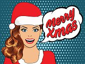 beautiful girl in santa claus clothes. pop art woman in christmas hat. christmas card with young woman in pop art style. poster with Woman in Pop Art style with Merry Xmas bubble.