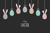 Beautiful hanging Easter eggs with bunnies and greetings. Vector