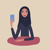 Lovely happy young girl Beautiful Muslim woman wearing hijab sitting at table holding mobile phone in her hand Taking picture Make selfie Modern Technology concept Beige background Pretty Cute Lovely.