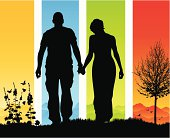 Beautiful romantic couple holding hands in silhouette on a walk in the country.