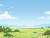 Illustration of a beautiful idyllic landscape with flowers, hills, bushes, trees, a lake and mountains in the far distance, and a blue, cloudy sky with space for text.