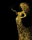 Beautiful Woman abstract figure formed by gold color particles on the black background. Bright banner with beautiful glamour girl with hair down and in fashion dress.