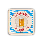 A refreshing pint of cold beer sitting on a bar coaster with a gradated blue background.