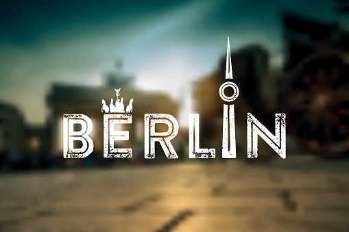 Berlin text sign on blurred city background