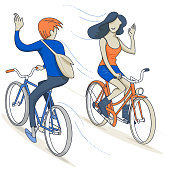 A man and a woman wave to each other while riding thaeir bikes