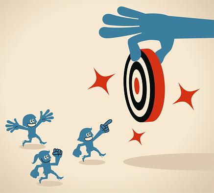 Big hand gives group of people (team members, businesswomen, women power) a new goal (dart board, target)