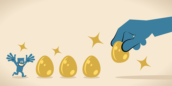 Big hand is giving golden eggs to entice (motivate) a businessman
