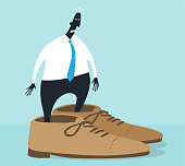 An office worker trying to wear really big shoes for him.