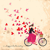 Beautiful girl wearing bandana pony tail black blouse long red skirt ballerinas rides a retro-style pink bicycle with basket full of hearts spreads good mood love joy freedom magenta hearts and birds flying like a fresh breeze. Original artwork illustration square shape on yellowish old-paper background with typography.