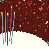 A bright colorful scene of festive candles and confetti with copy space on the cake for your message.