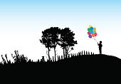 Silhouette of a boy in a big open field holding colorful helium balloons