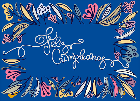Birthday greeting in Spanish. Text says Happy Birthday. Floral frame and hand lettering