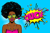 Ouch, oops, surprise. Black african-american young girl in glasses. Woman pop art. Comic text advertise speech bubble. Retro halftone background.