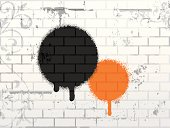 A black and an orange circle painted onto white brick
