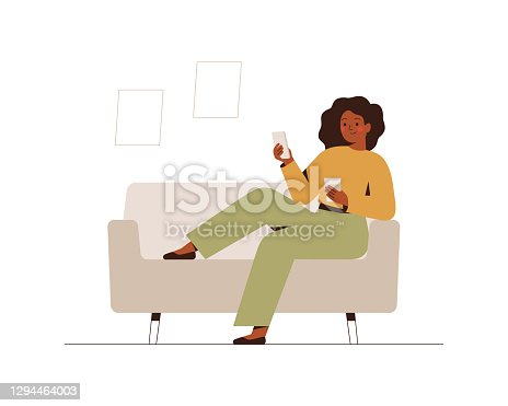 Black businesswoman sits on the couch at home or in the office with a mobile phone at break time.