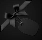 Vector illustration of black gift bow with black tag on black background.