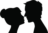 Silhouette of man and woman head profile . Couple kissing