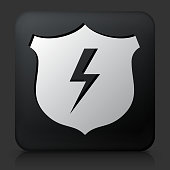 Black Square Button with Shield & Lightning. This royalty free vector image features a white interface icon on square black button. The vector button has a bevel effect and a light shadow. The image background is dark grey and the button has a light reflection.
