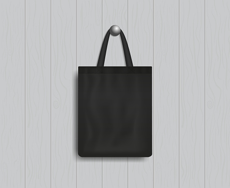 Black tote on wood wall. Mockup of eco canvas bag with handle. Cotton fabric tote. Reusable cloth of ecobag for shopping, grocery, market, beach. Realistic fashion handbag. Template of design. Vector