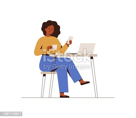 Black Woman chatting on a smartphone sitting at the cafe table. Happy freelancer or office female working remotely use a laptop. African girl looking at the phone, drinking coffee at the workplace.