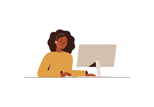 Black woman with a headset is working at the computer in the call center or support department