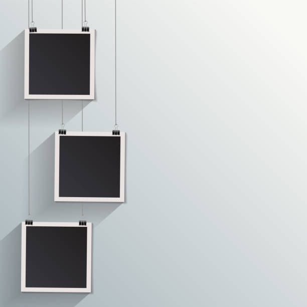 Blank retro vintage photo frames on a wall Blank retro vintage photo frame set hanging on a clip. Realistic detailed photo icon design template. Vector isolated on white wall background. photo album stock illustrations