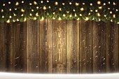 Blank wooden background with bright garland and falling snow
