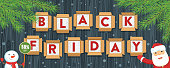 Black friday sale banner. Letters are in cardboard boxes on black background. Santa Claus and snowman
