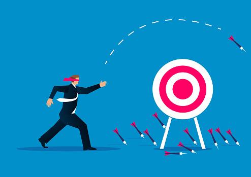 Blind, businessman blindfolded throwing darts at target