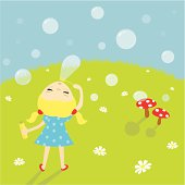 Little girl blowing bubbles on the green field with daisies.