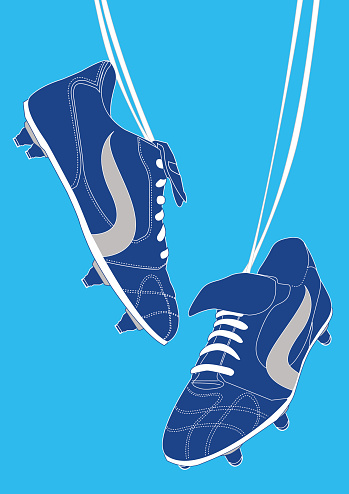 Blue football shoes on light blue background.